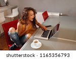 young surprised woman typing on ... | Shutterstock . vector #1165356793