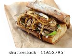 Steak sandwich ~ toasted baguette with grilled beef and onions, on goat's cheese and spinach leaves.  On a brown bag, for a tasty lunch to go. - stock photo