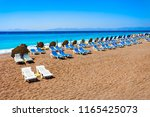 sunbeds with umbrellas at the... | Shutterstock . vector #1165425073