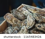 oysters on the counter in... | Shutterstock . vector #1165483426