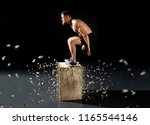 man jumping on fit box in gym.... | Shutterstock . vector #1165544146