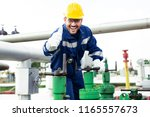 worker closes the valve on the... | Shutterstock . vector #1165557673
