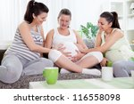 two female friends touching tummy of pregnant woman - stock photo
