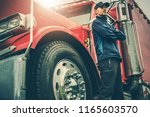 American Trucker Proud. Semi Truck Driver in Front of His Awesome Machine. Transportation Industry Theme. - stock photo