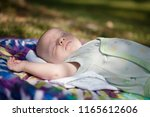 a baby napping outside on a... | Shutterstock . vector #1165612606