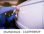 Car theft : The thief steals a white car in the parking lot using the right door unlocking tool. - stock photo