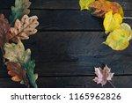 dry fall foliage on wooden desk.... | Shutterstock . vector #1165962826