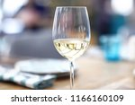 glass of white wine in the... | Shutterstock . vector #1166160109