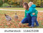 Family Feeding Ducks In The Park