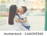 mom and son kissing together... | Shutterstock . vector #1166345560