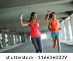 two female friends jogging and... | Shutterstock . vector #1166360329
