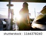 bearded man pumping gas in car... | Shutterstock . vector #1166378260