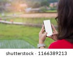 female holding phone at flied... | Shutterstock . vector #1166389213