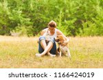 Stock photo portrait of cat and dog s interaction in their owner arms 1166424019