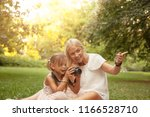 mom and daughter using photo... | Shutterstock . vector #1166528710