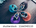 Small photo of High top angle view of multiethic hipster youngster sit in multi-colored armchairs in the loft room and make v-sign like big circle star sit chair bag color
