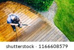 man cleaning terrace with a power washer - high water pressure cleaner on wooden terrace surface - stock photo
