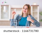 woman taking pills to cope with ... | Shutterstock . vector #1166731780