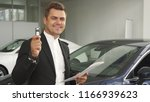 Small photo of A satisfied buyer reread the contract of buying a car. He shows the keys to his new car. He smiles. Men are in the car showroom