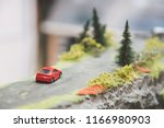 red car toy driving on the... | Shutterstock . vector #1166980903