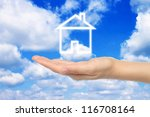 Virtual house with woman hand on sky background - stock photo