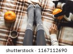 Stock photo women s hands and feet in sweater and woolen cozy gray socks holding cup of hot coffee sitting on 1167112690