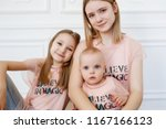 Small photo of Light family series. Three sisters on a white background, dressed in funny t-shirts and jeans