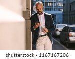 handsome businessman leaning on ... | Shutterstock . vector #1167167206