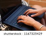 hands typing in a black laptop. | Shutterstock . vector #1167325429