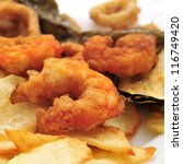 closeup of a plate with battered and fried shrimps served as tapas with potato chips - stock photo