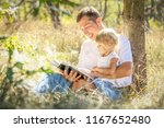 happy parent reading with child ... | Shutterstock . vector #1167652480