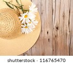 sun hat and daisies on wooden... | Shutterstock . vector #116765470