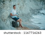 young handsome man sitting on a ... | Shutterstock . vector #1167716263