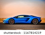 Small photo of Dubai / United Arab Emirates - 04/05/2018: The Lamborghini Aventador S supercar on a quiet Dubai road in the desert, in front of a red Fiat 500