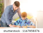 father helping son with... | Shutterstock . vector #1167858376