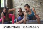 three sportswomen stretching at ...   Shutterstock . vector #1168266379