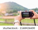 women holding camera at nature... | Shutterstock . vector #1168426600