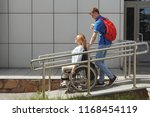 woman in a wheelchair using a...   Shutterstock . vector #1168454119