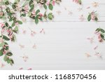 Stock photo branches of bush with pink flowers on wooden background 1168570456