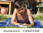 Teenage boy reading a book while sunbathing in a garden - stock photo