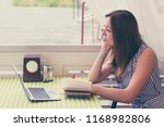 Small photo of Waist-up portrait of young talented female writing poem in notebook. Attractive girl in brooding mood looking out window. Model with beautiful brunette hair