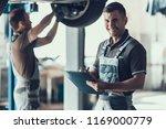 mechanics checking wheel... | Shutterstock . vector #1169000779