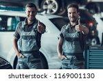 two handsome happy auto... | Shutterstock . vector #1169001130