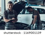 two handsome happy auto... | Shutterstock . vector #1169001139