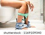 woman in bathroom using toilet. | Shutterstock . vector #1169109340