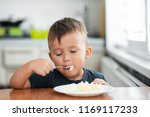 the little boy in the kitchen... | Shutterstock . vector #1169117233