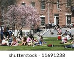 college students enjoying spring weather on campus - stock photo