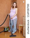 pregnant woman cleans with vacuum cleaner at home - stock photo