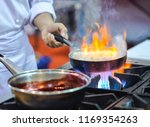 chef frying meat on the gas... | Shutterstock . vector #1169354263
