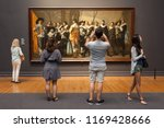 """Small photo of Amsterdam, Netherlands - May 2018: Tourists look at a painting of """"The Meagre Company"""" (by Frans Hals and Pieter Codde) displayed at the Rijksmuseum"""